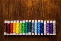 Bobine du fil de diverses couleurs sur le bureau en bois Photographie stock libre de droits