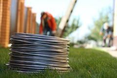 Bobine en aluminium de fil sur l'herbe Matériaux, industrie images libres de droits
