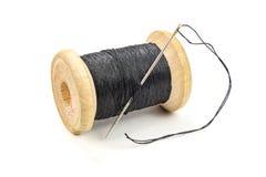 Bobine en bois de vintage de fil et d'aiguille noirs sur le fond blanc Photo libre de droits