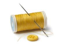 Bobine jaune, aiguille et bouton de couture Image libre de droits
