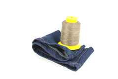 Bobine jaune de coton sur le tissu bleu de denim Images libres de droits