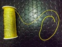 bobine jaune de fil, sur une surface noire Images libres de droits