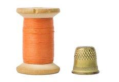 Bobine orange et dé de fil d'isolement sur le blanc Images stock