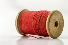 Bobine ou bobine du fil de couture rouge d'isolement sur le blanc De peu profond Image stock