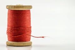 Bobine ou bobine du fil de couture rouge d'isolement sur le blanc De peu profond Photos stock