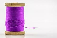 Bobine ou bobine du fil de couture violet sur le blanc shallow Images stock