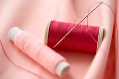 Bobine rouge de fil sur le tissu Image libre de droits
