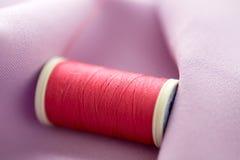 Bobine rouge de fil sur le tissu Images stock