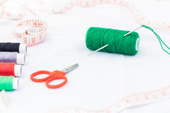 Bobine verte de fil avec l'aiguille et les ciseaux Photo libre de droits