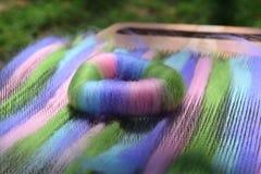 Bobine verte, rose, bleue, et pourpre de rolag de laine sur un conseil de mélange Photographie stock libre de droits