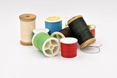 Bobines assorties de fil sur le fond blanc Image stock