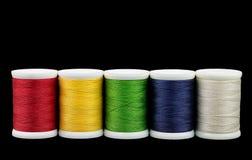 Bobines avec des amorçages de couleur Plusieurs bobines de fil coloré sur un fond noir Image stock