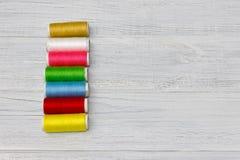 Bobines avec les fils colorés sur le vieux fond en bois de table, Photo stock