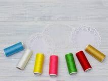 Bobines avec les fils colorés sur le vieux fond en bois de table, Images stock