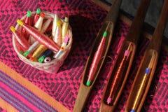 Bobines colorées dans le panier et la bobine en bois sur le tissu en soie Photo stock