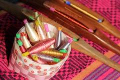 Bobines colorées dans le panier et la bobine en bois sur le tissu en soie Images stock