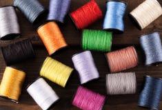 Bobines colorées de coton dispersées sur le bois foncé Photo libre de droits