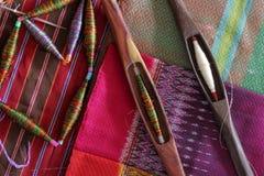 Bobines colorées et bobine en bois sur le tissu en soie Photo stock