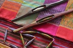 Bobines colorées et bobine en bois sur le tissu en soie Photographie stock libre de droits