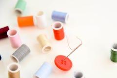 Bobines colorées multi de fil, aiguille et bouton rouge Photo libre de droits