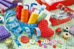 Bobines de fil coloré, boutons, tissus, bande de mesure, goupille Photos libres de droits