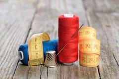 Bobines de fil, d'aiguille, de bande de mesure et de dé Images stock