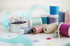Bobines de fil et d'outils de couture de base comprenant les goupilles, l'aiguille, un dé, et le ruban métrique Photos libres de droits