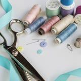 Bobines de fil et d'outils de couture de base comprenant les goupilles, l'aiguille, un dé, et le ruban métrique Photos stock
