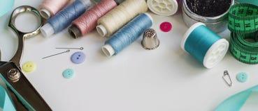 Bobines de fil et d'outils de couture de base comprenant les goupilles, l'aiguille, un dé, et le ruban métrique Images stock