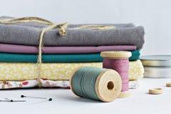 Bobines de fil de vintage, goupilles, boutons en bois, pot en métal et tissus de coton photos stock
