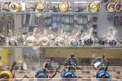 Bobines de pêche dans un coffret en verre de boutique d'attirail Images stock