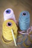Bobines de rose, de jaune, et Gray Yarn et une aiguille de crochet Images stock