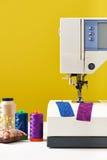 Bobines des fils à côté de la machine à coudre sur le fond jaune Photo libre de droits