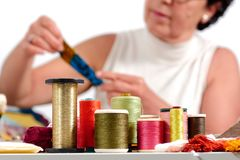 Bobines des fils colorés, ouvrière couturière au fond Photo stock