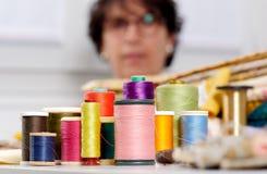 Bobines des fils colorés, ouvrière couturière au fond Photographie stock libre de droits