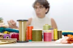 Bobines des fils colorés, ouvrière couturière au fond Photo libre de droits