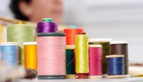 Bobines des fils colorés, ouvrière couturière au fond Image stock