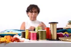 Bobines des fils colorés, ouvrière couturière au fond Images libres de droits