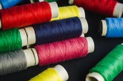 Bobines des fils colorés sur un tissu noir photographie stock