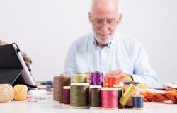 Bobines des fils colorés, tailleur d'homme au fond Photos stock