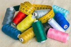 Bobines des fils de différentes couleurs, bande de mesure sur la lumière b Photo stock