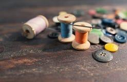 Bobines des fils et des boutons sur la vieille table en bois Image stock