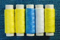 Bobines du fil de couture blanc, jaune et vert disposé dans la rangée sur le denim image stock