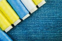 Bobines du fil de couture blanc, jaune et vert disposé dans la rangée sur le denim avec l'espace de copie photos stock