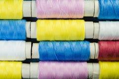 Bobines du fil de couture bleu, jaune et rose disposé dans les rangées sur le denim photographie stock libre de droits