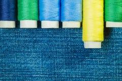 Bobines du fil de couture bleu, jaune et vert disposé dans la rangée sur le denim avec l'espace de copie images stock