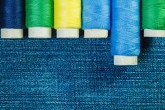 Bobines du fil de couture bleu, jaune et vert disposé dans la rangée sur le denim avec l'espace de copie photographie stock libre de droits