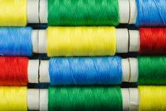 Bobines du fil de couture bleu, jaune, rouge et vert disposé dans les rangées sur le denim photographie stock
