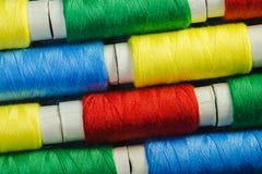 Bobines du fil de couture bleu, jaune, rouge et vert disposé dans les rangées sur le denim images stock