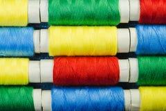 Bobines du fil de couture bleu, jaune, rouge et vert disposé dans les rangées sur le denim image libre de droits